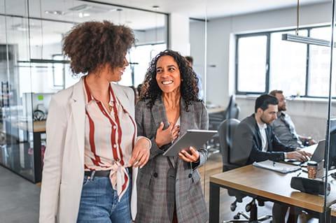 two ladies walking in the office talking