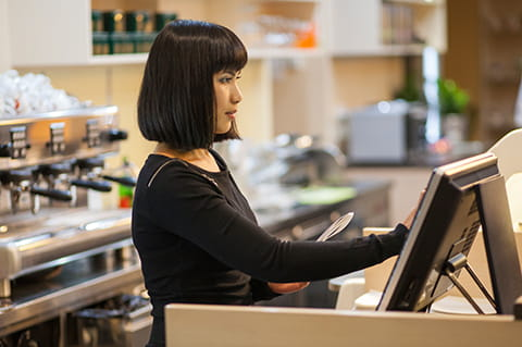 Lady with black hair working on till