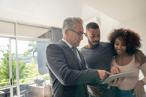 Real estate agent showing couple info on a tabled