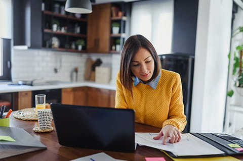 Woman at home desk orange shirt laptop
