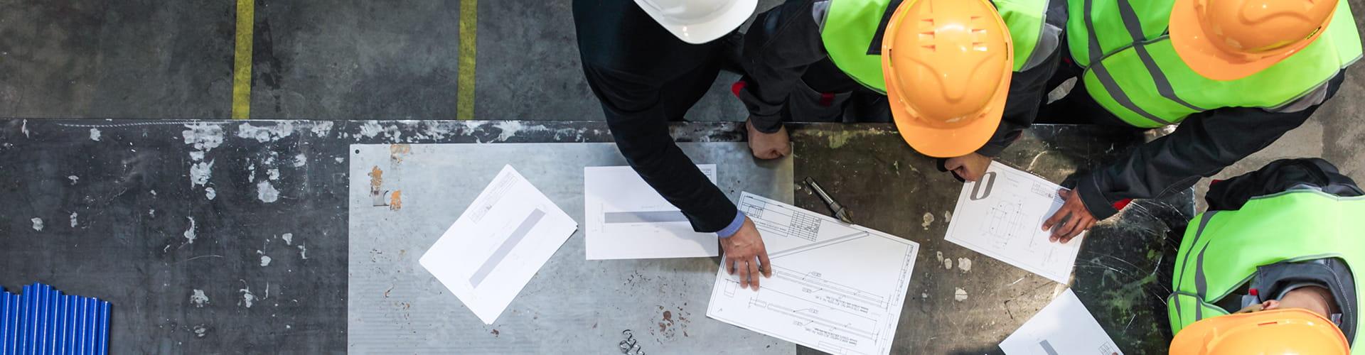 Workers in hard hats looking over paperwork