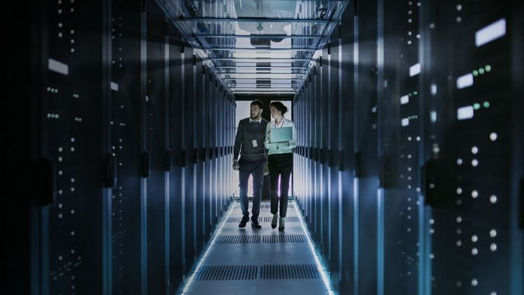 Two people walking in  a server room
