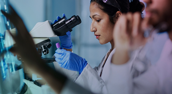 A woman looking through a microscope at a sample