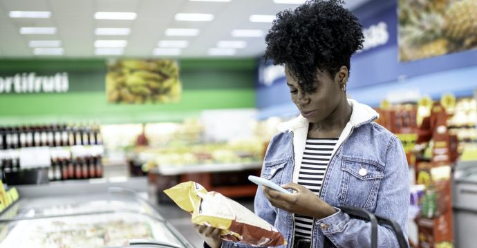 A lady holding a packet of chips at a supermarket