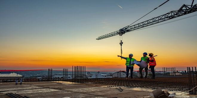 Three men on a construction site with a crane in the background