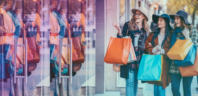Three ladies carrying colourful bags doing window shopping