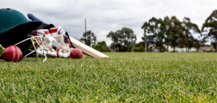 Cricket helmet and bat on the grass