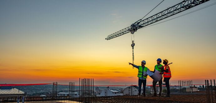 Men standing on top of a building site with a crane in the background