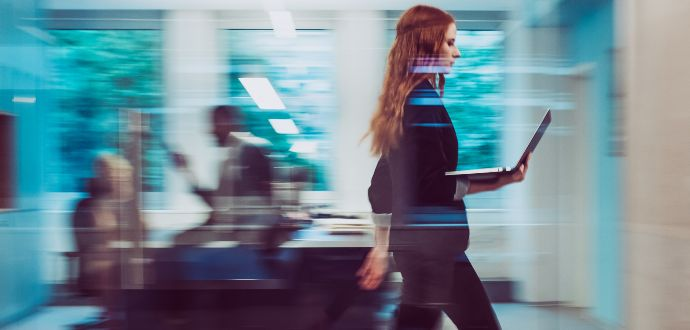 Business professional walking with a  open laptop