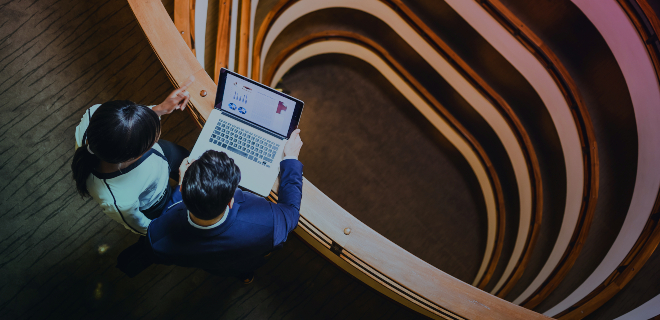 Colleagues looking at the laptop from the top of the stairs