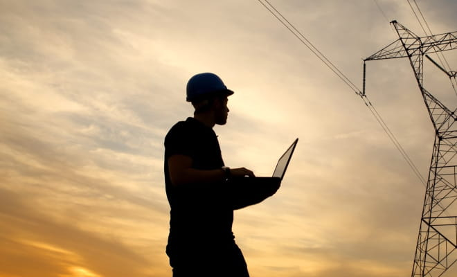 A man silhouetted against a pylon and sunset