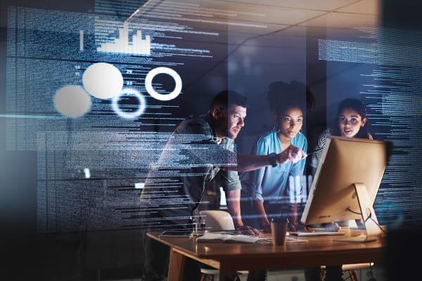 Three people looking at a monitor