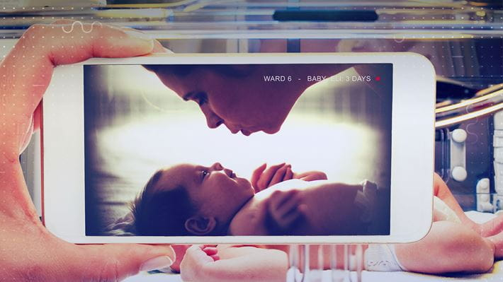 A photo on a screen of a mother going to kiss her baby