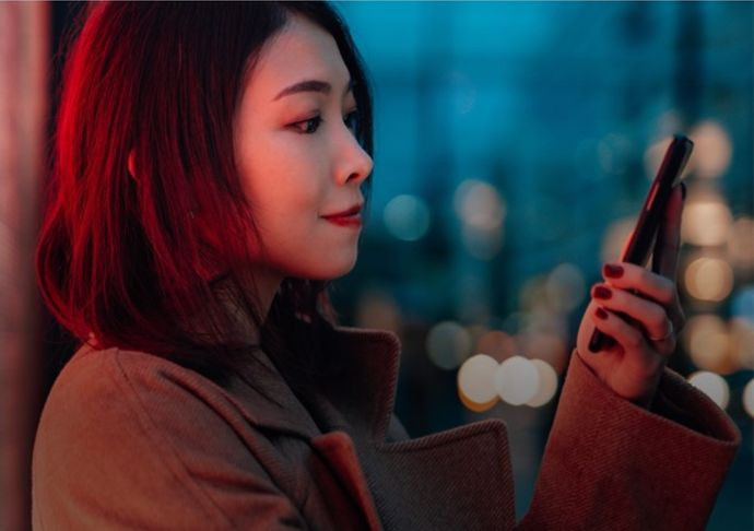 Woman smiling at her mobile phone