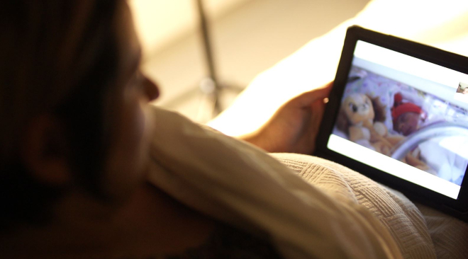 A woman looking at her newborn on an iPad