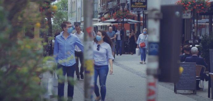 People walking in a street wearing preventative masks