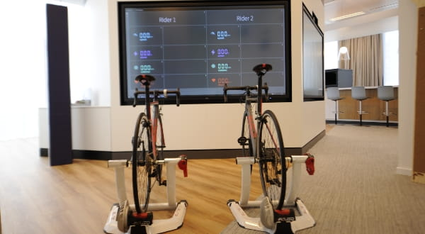 Two bicycles with a sceen behind