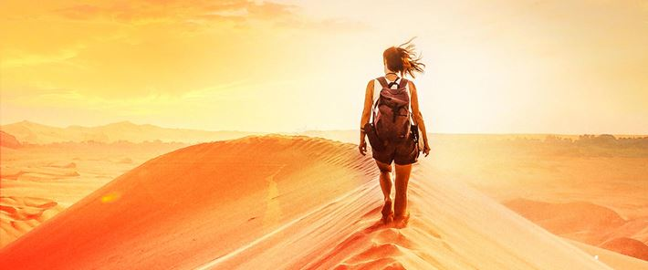 A woman walking on top of a sand dune
