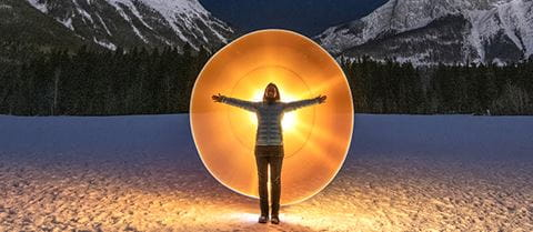 Woman with open arms standing in front of a glowing circle