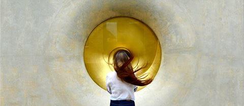 Woman standing in front of metallic orb