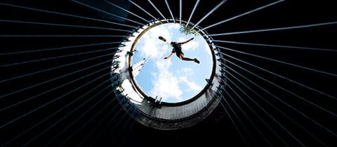 Man jumping over the top of a silo