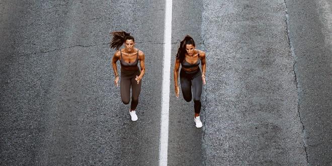 Two women running down a tar road