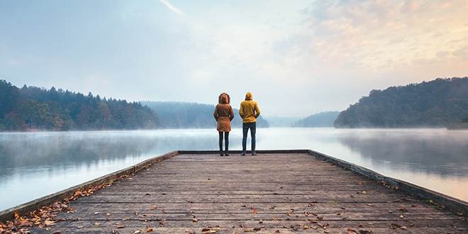 Two people standing at the end of a dock overlooking a lake