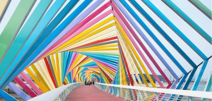 People walking on a colourful bridge