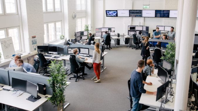 People sitting and standing in an open-plan office