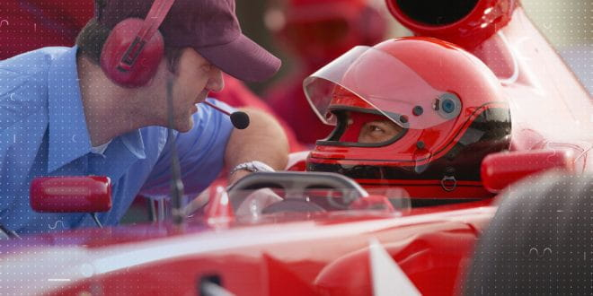 Formula 1 driver talking to a crew member
