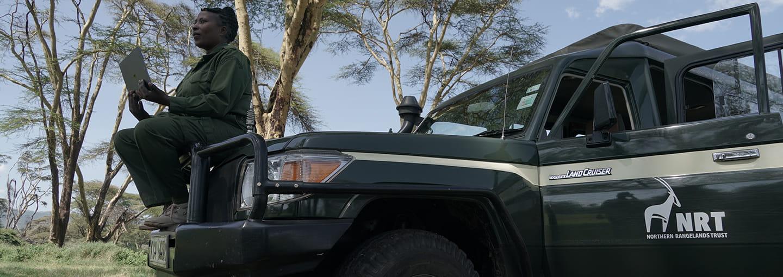 A Kenyan park ranger sitting on a park vehicle