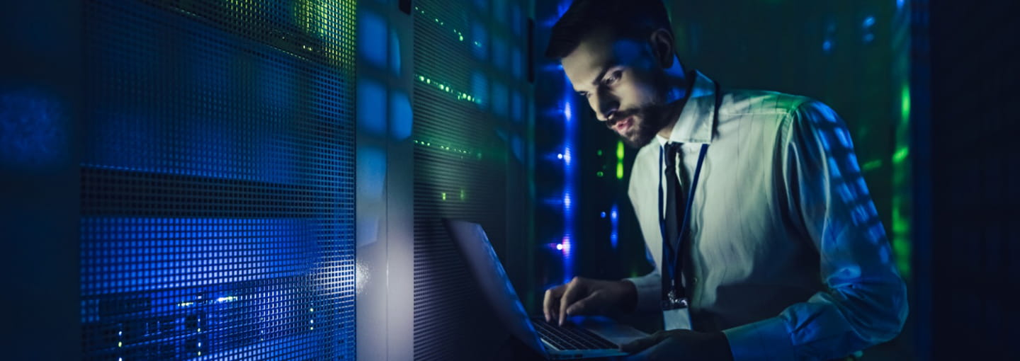 Man working on laptop in data centre