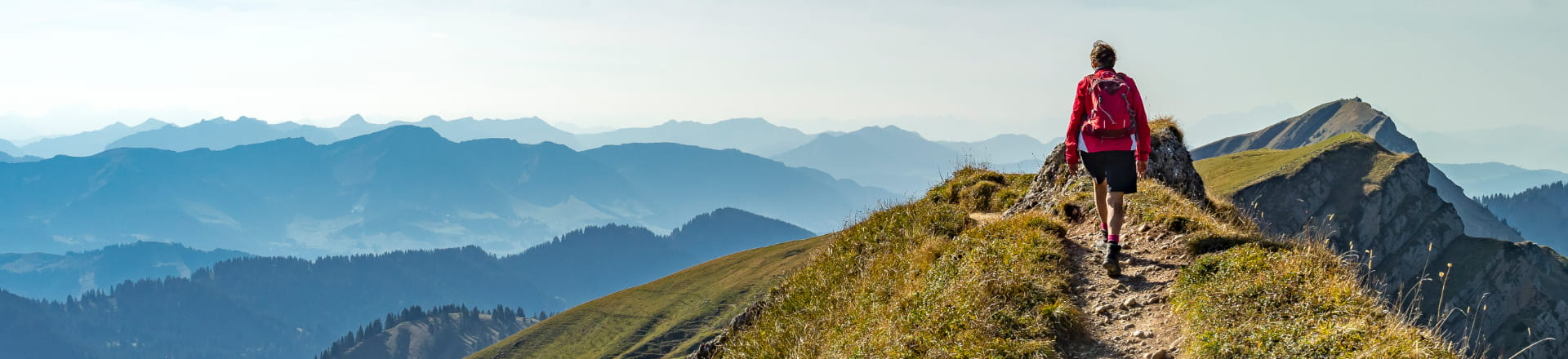 Hiker leading the way at the top of a mountain
