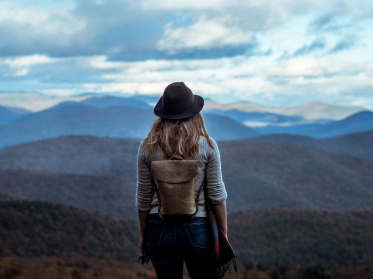 Woman wearing hat and backpack overlooking a valley