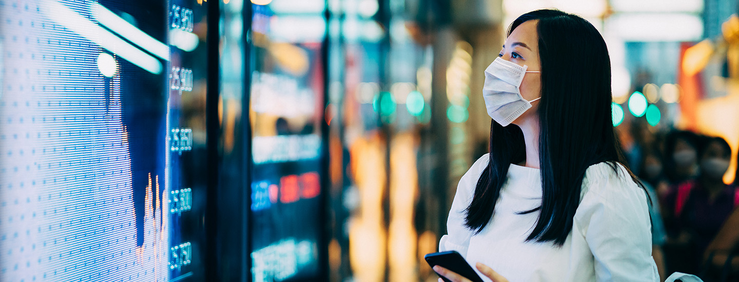 Woman with mask looking at screens