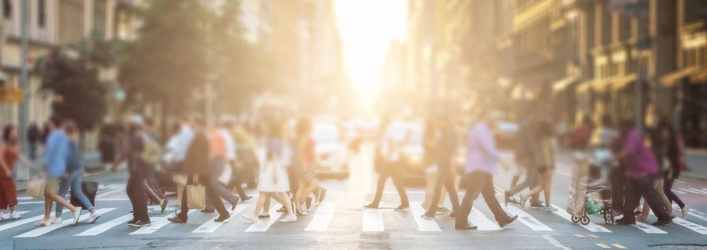 A busy street of people walking across a crossroad