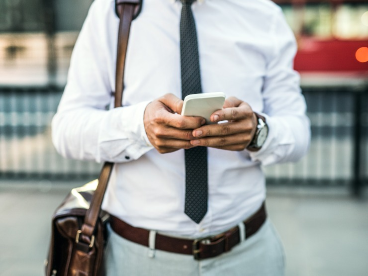 A photo of a man's torso and hands as he uses a phone