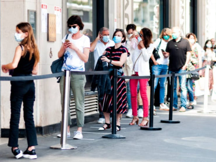 People standing in a queue with masks