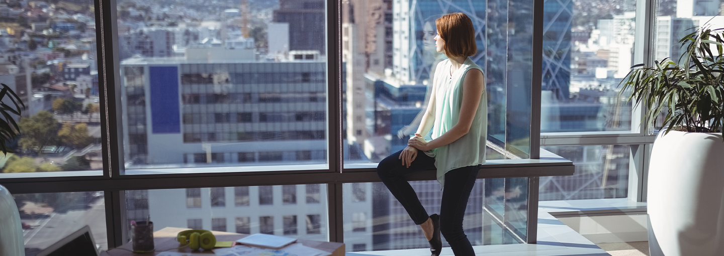 Female looking out of office window at city below
