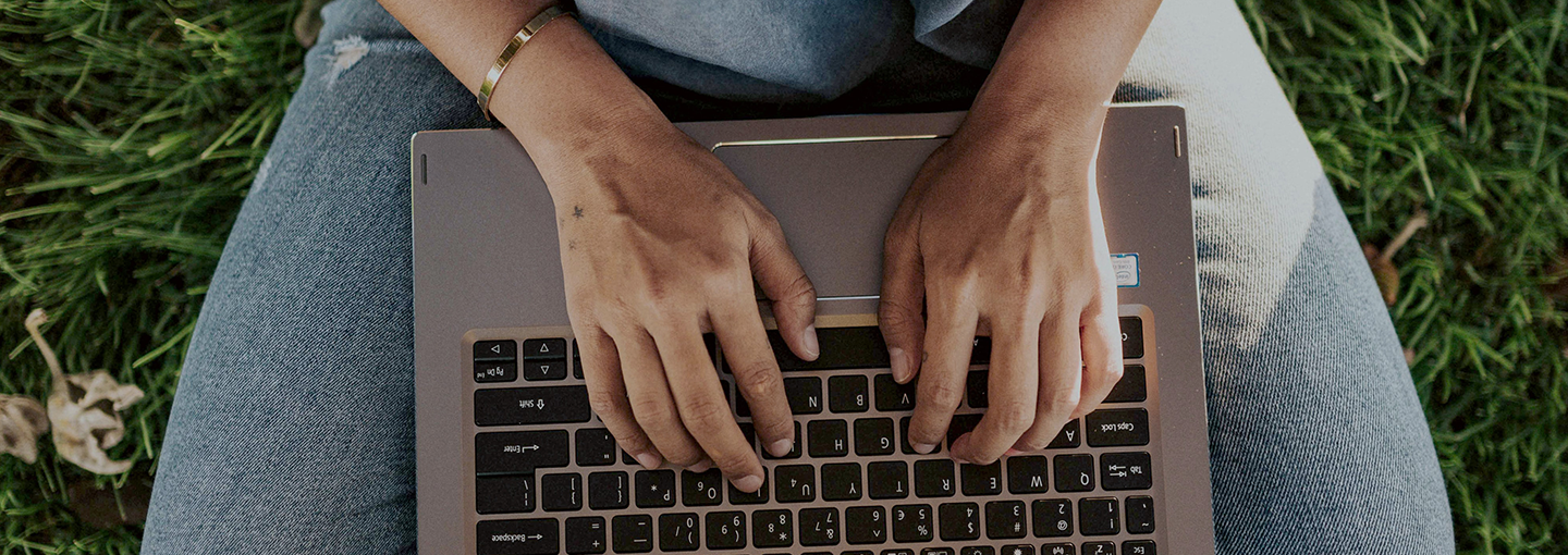 Aerial view of hands on a laptop keyboard on a lap