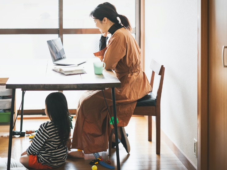 A woman working from home with her daughter