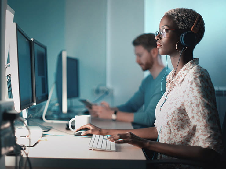Woman wearing headphones sitting at a computer