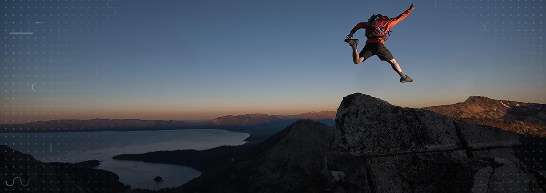 Hiker jumping above peaks