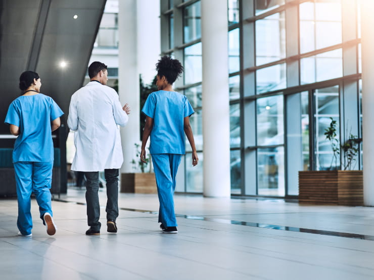 Doctors walking in a hall with glass walls