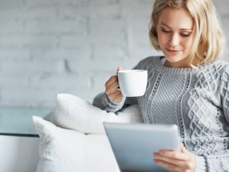 A woman sitting on the couch with a tablet and mug