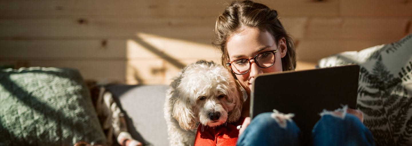 Woman working on tablet while her dog watches