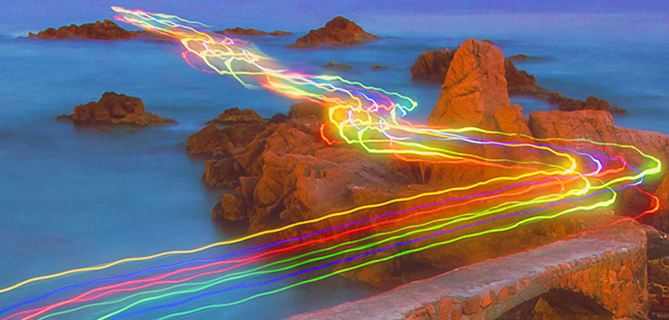 Road with colourful light trails at a body of water
