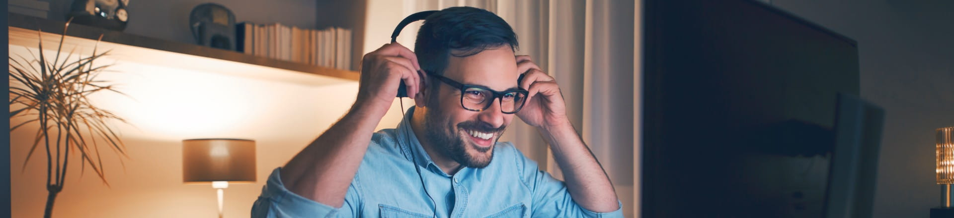 A man wearing a headset while working from home