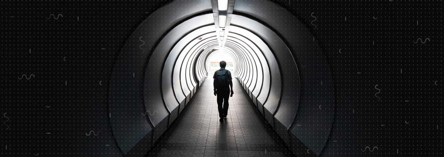 A person walking down a tunnel towards the exit