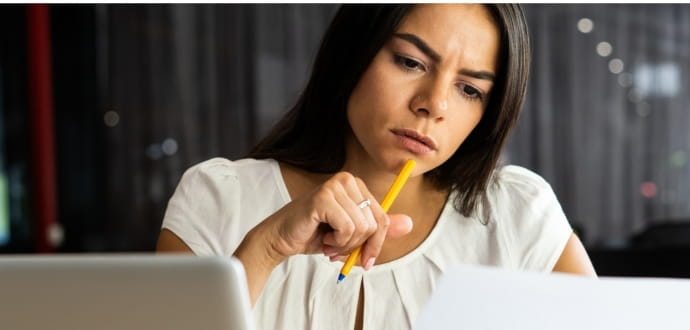 Woman looking at screen in thought